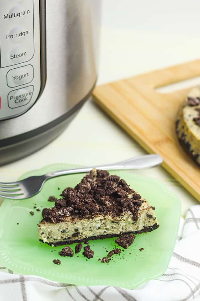 Instant Pot Oreo Cheesecake on a plate with a fork and pieces of oreo