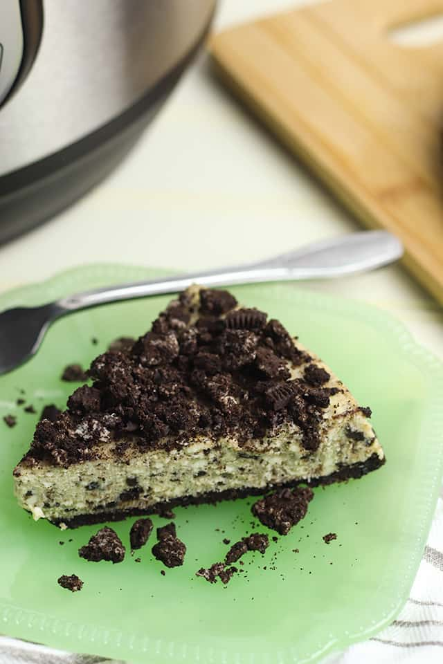 close-up pressure cooker oreo cheesecake on a green dessert plate with fork