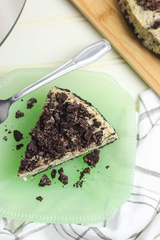 overhead shot of instant pot oreo cheesecake on a green plate with a striped linen