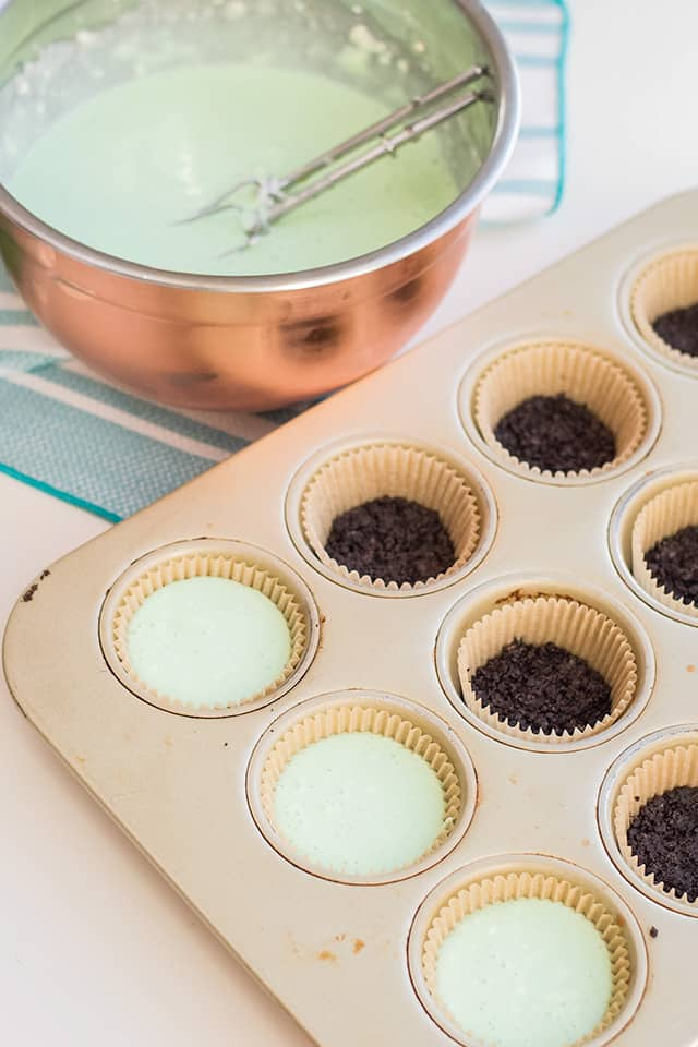 adding mint cheesecake batter to a cupcake pan with a mint oreo crust