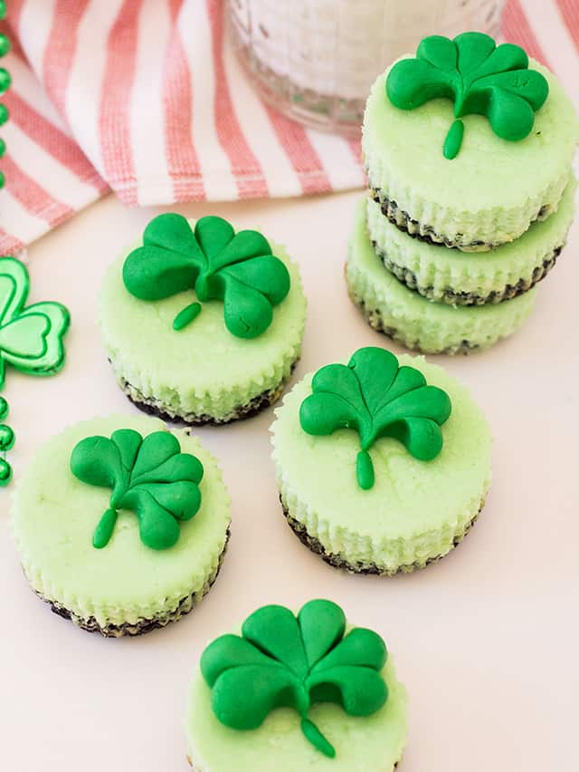 mini mint cheesecakes with fondant shamrocks on a striped linen