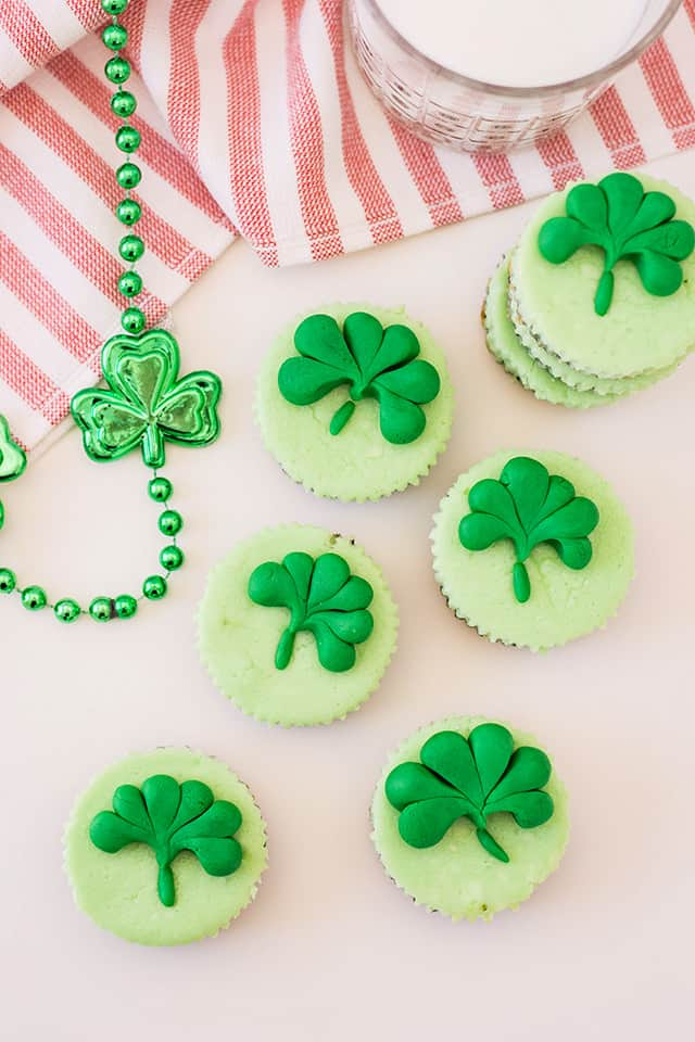 mini baked mint cheesecakes with a shamrock embellishment and glass of milk