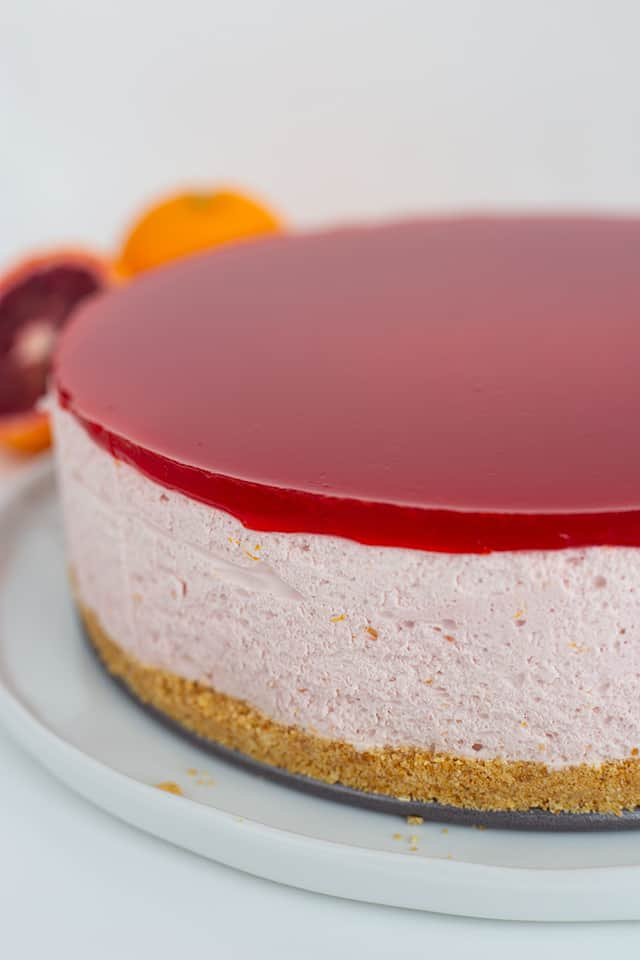 whole blood orange cheesecake on a white platter