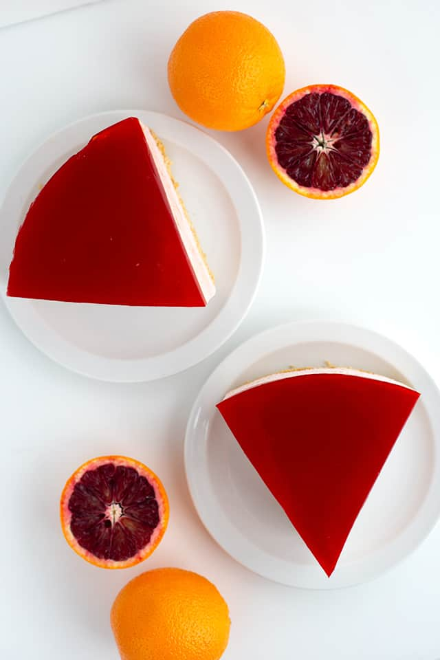overhead photo of two slices of blood orange cheesescake on white dessert plates with oranges scattered