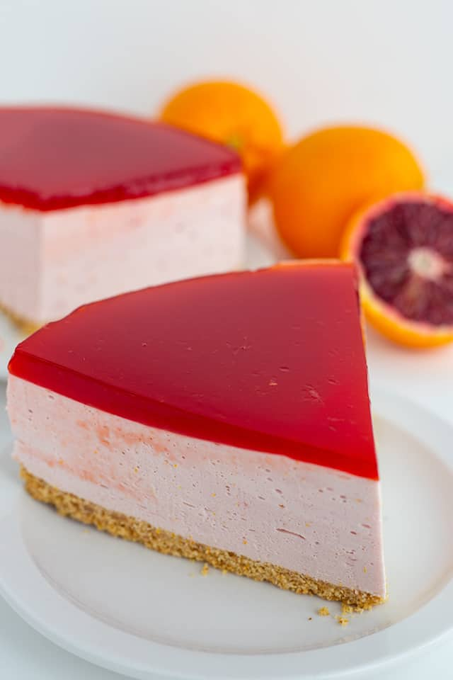 slice of blood orange cheesecake on a white plate with a sliced orange
