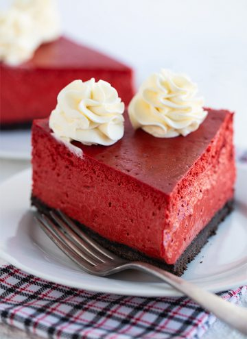 slice of red velvet cheesecake on a white plate with fork