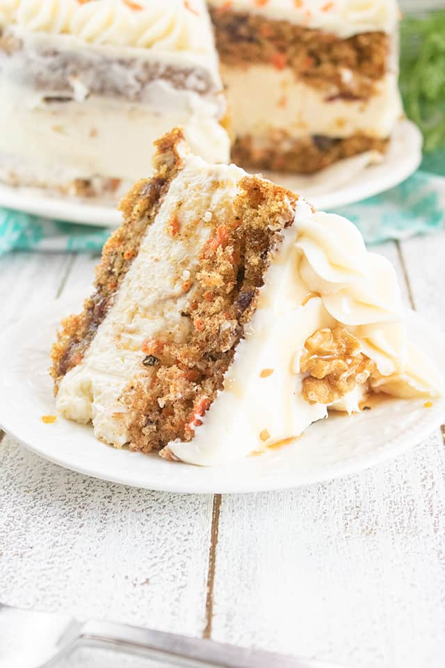 slice of carrot cake cheesecake cake on a white plate