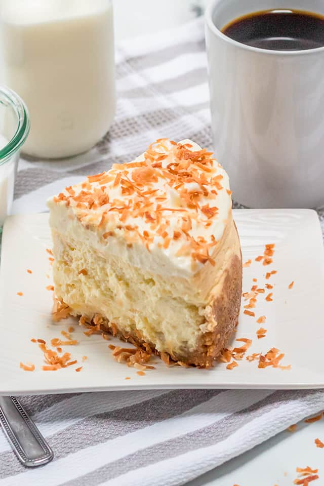 slice of instant pot cheesecake on a white square plate with toasted coconut