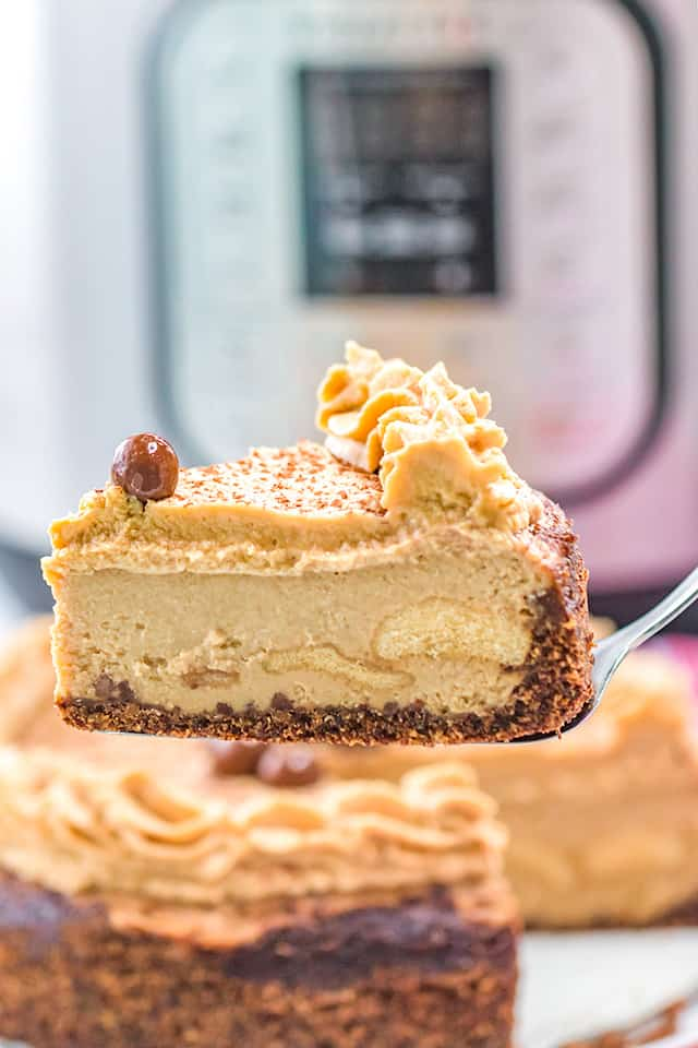 Pie server holding a slice of tiramisu cheesecake with an instant pot in the background
