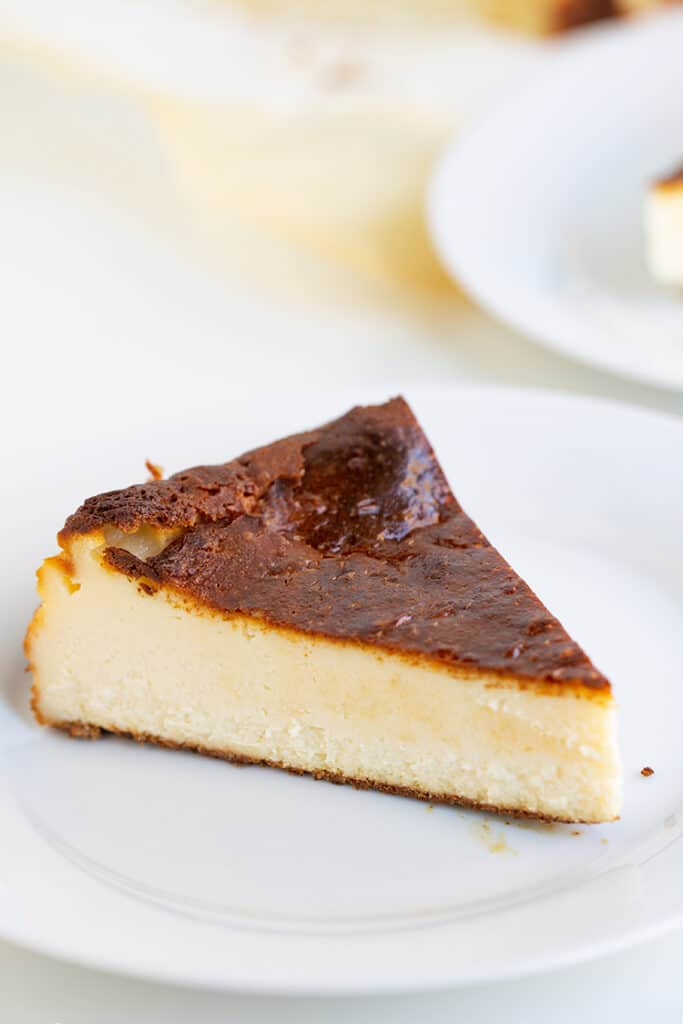 slice of burnt cheesecake on a white plate on a white surface