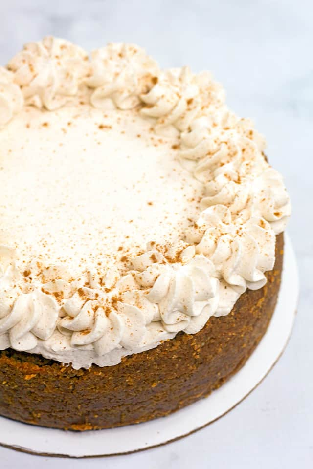 whole cheesecake with whipped cream and cinnamon on top on a marble surface