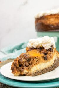 slice of pecan pie pumpkin cheesecake on a white plate with a blue charger
