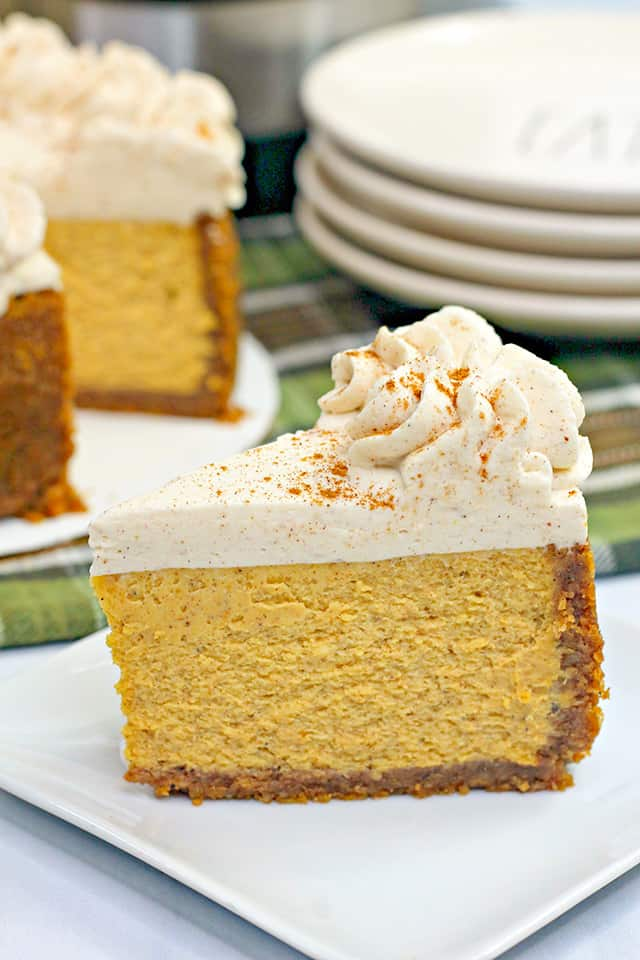 Close up of sliced pumpkin cheesecake with the rest of the cheesecake behind it