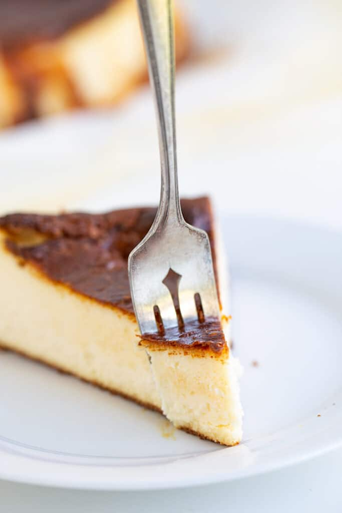 slice of cheesecake on a white plate with a fork in it