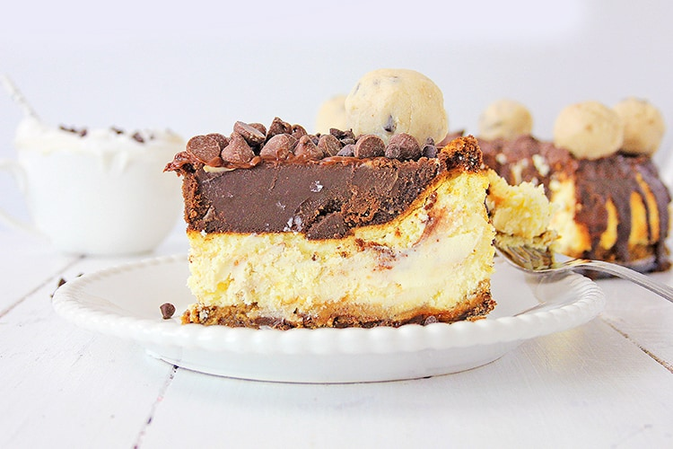 horizontal photo of the side of a cheesecake on a white plate with a bowl behind it