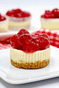 mini cheesecake on a square white plate with a red and white checked linen behind it