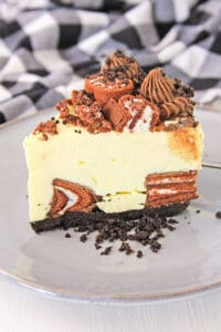 a slice of cheesecake on a gray plate with oreo crumbs beside the slice