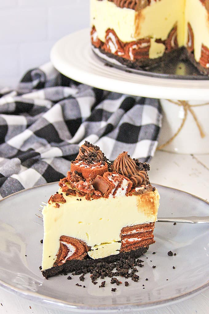 slice of cheesecake on a gray plate with a plaid linen behind it